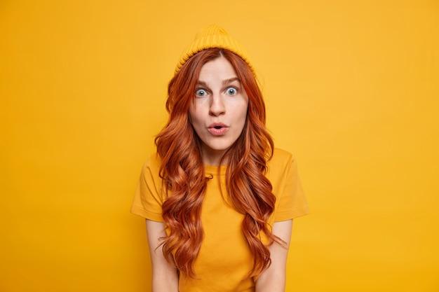 Une fille rousse choquée regarde sans voix, a l'expression du visage étoilé ouvre la bouche d'étonnement porte un t-shirt décontracté