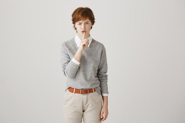 Fille rousse en colère avec coupe courte posant contre le mur blanc