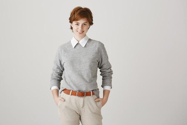 Fille rousse confiante avec coupe de cheveux courte posant contre le mur blanc