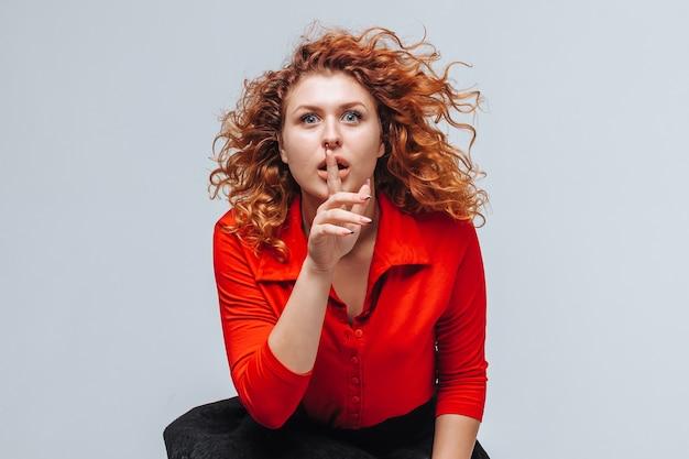 Fille rousse a couvert sa bouche avec un doigt. le concept du secret
