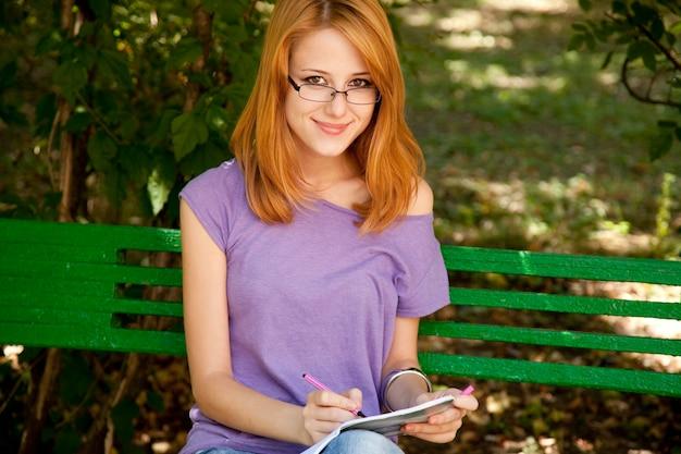 Fille rousse dans des verres à faire ses devoirs dans le parc.