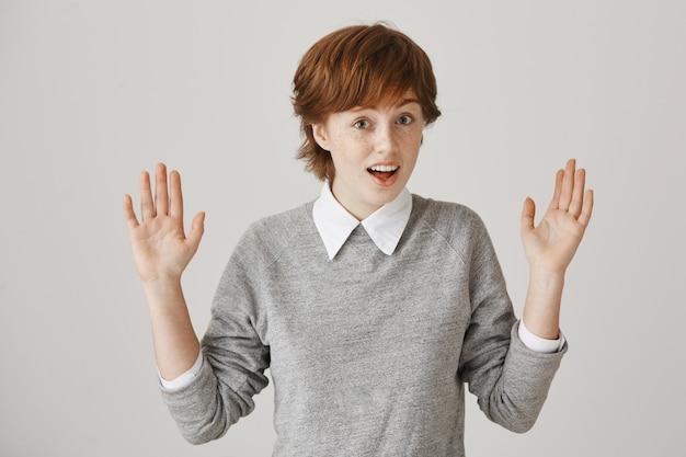 Fille rousse désemparée et confuse avec une coupe de cheveux courte posant contre le mur blanc