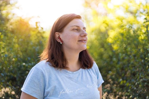 Fille rousse écoute de la musique et aime se détendre dans le parc au soleil couchant en été
