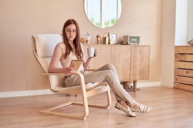 Fille rousse est assise dans un fauteuil et tient une tasse et se penche sur le carnet de croquis dans un intérieur confortable