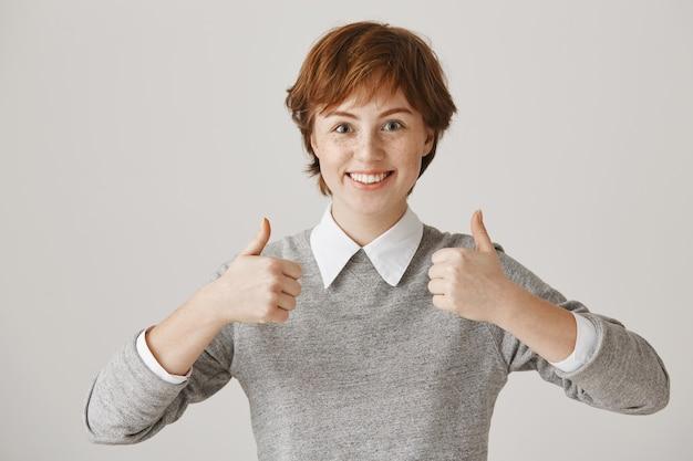 Fille rousse excitée et satisfaite avec une coupe de cheveux courte posant contre le mur blanc