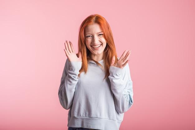 Fille rousse excitée en studio sur fond rose