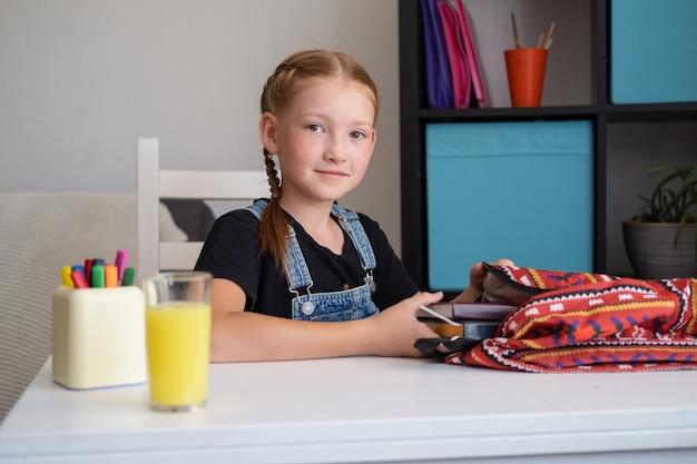 Fille rousse heureuse dans le sac à dos d'emballage de lunettes, se préparant à l'école. retour au concept de l'école.