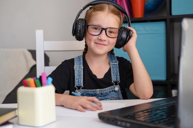Fille rousse heureuse à lunettes écouter dans les écouteurs tout en étudiant à la maison. retour à l'école