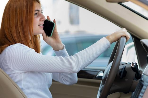 Fille rousse heureuse parler sur son téléphone portable au volant d'une voiture.