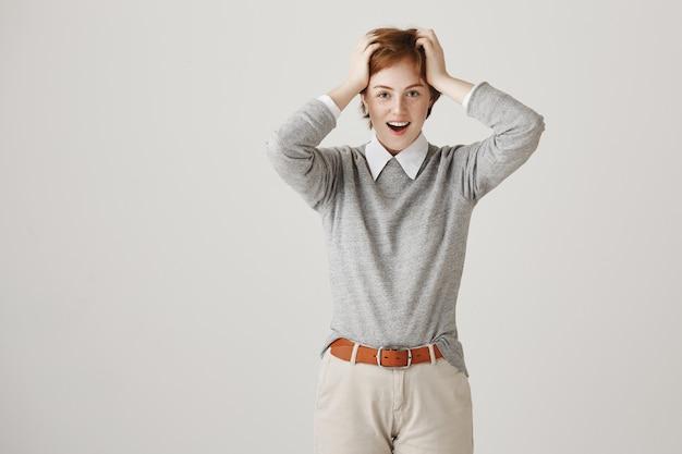 Fille rousse insouciante avec coupe de cheveux courte posant contre le mur blanc