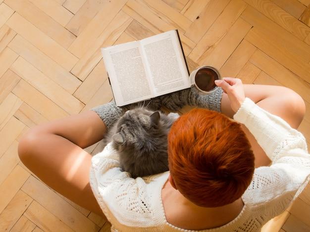 Fille rousse lisant un livre avec une tasse de thé à la main et son chat