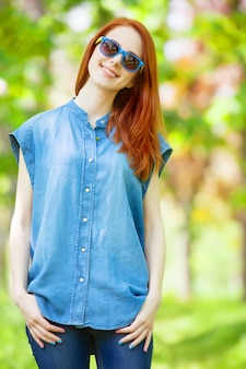 Fille rousse avec des lunettes de soleil dans le parc au printemps.