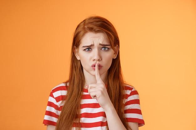 Une fille rousse mal à l'aise et insécurisée qui supplie de garder le secret en toute sécurité, grimace en fronçant les sourcils, pressée de faire taire ...