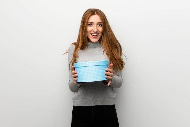 Fille rousse sur un mur blanc surprise car elle a reçu un cadeau