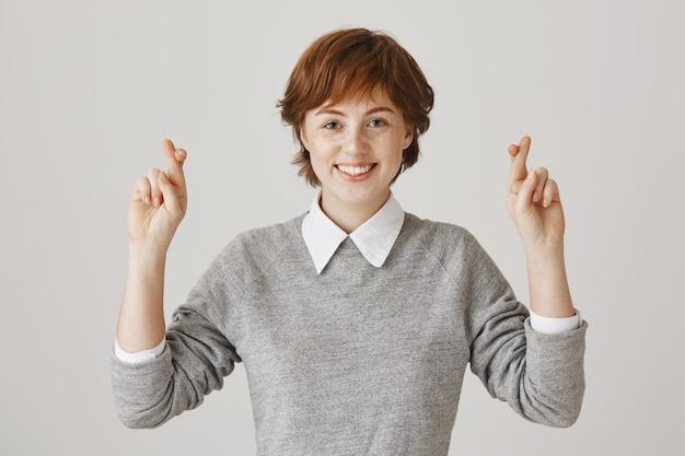 Fille rousse pleine d'espoir avec une coupe de cheveux courte posant contre le mur blanc