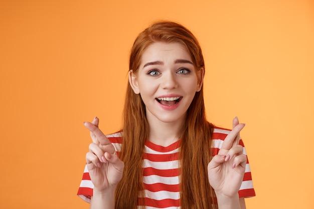 Une fille rousse pleine d'espoir espère gagner à la loterie, souriante optimiste, regardez la foi, croyez que le rêve devient réalité, croisez les doigts bonne chance, faites un vœu, anticipez la bonne nouvelle, priez pour la fortune, fond orange