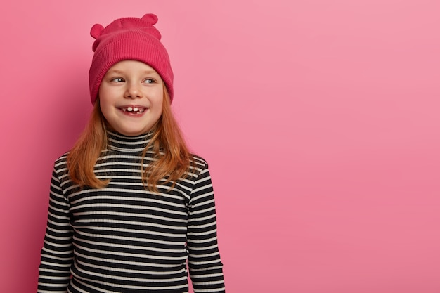Une fille rousse positive porte un chapeau et un col polo rayé, regarde de côté, remarque quelque chose d'amusé, se souvient avoir passé du bon temps avec les parents, pose sur un mur rose pastel, a une belle expression