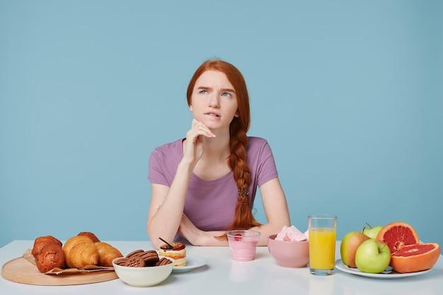 Fille rousse regardant vers le haut réfléchi à ce qu'il faut manger pour le petit déjeuner, s'assoit à une table sur laquelle se trouvent des produits de boulangerie et des fruits frais