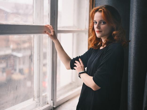 Fille rousse se tient près de la fenêtre