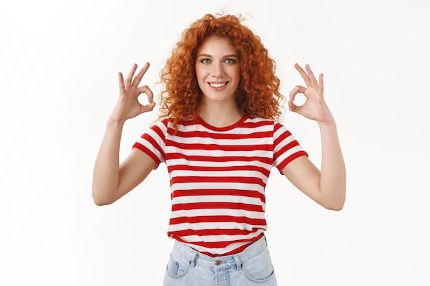 Une fille rousse séduisante et bouclée souriante et sûre d'elle montre d'accord ok geste parfait recommander un excellent magasin souriant heureux approuvant une bonne affaire comme tout, mur blanc