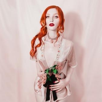 Fille rousse sexy avec les cheveux réunis en queue de cheval tenant une fleur lilas dans les mains. modèle de tatouage gothique en sous-vêtements érotiques avec une taille élancée. le vampire aux couleurs pastel.