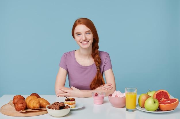 Fille rousse souriante aux cheveux tressés assis à une table, sur le point de prendre le petit déjeuner en regardant la caméra, isolée sur le mur bleu