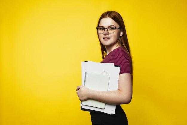 Fille rousse souriante caucasienne tient des cahiers et des fichiers dans les mains