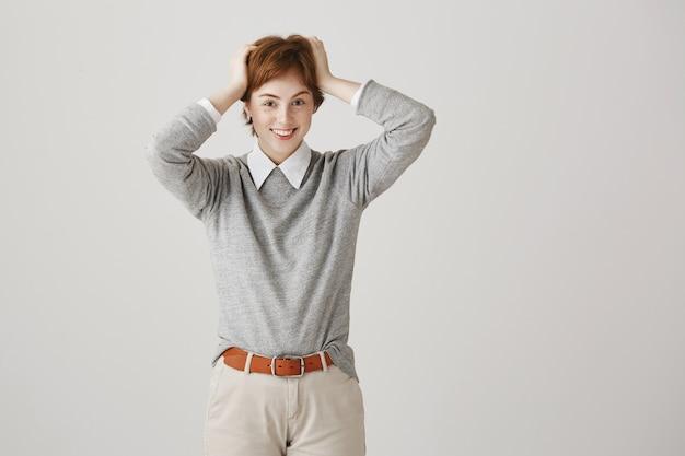 Fille rousse souriante insouciante avec coupe de cheveux courte posant contre le mur blanc