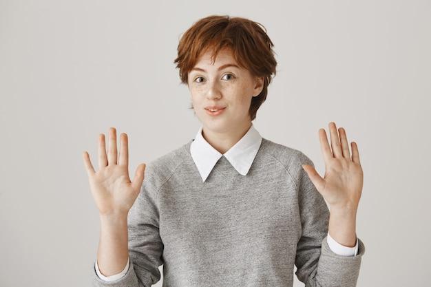 Fille rousse souriante maladroite avec coupe de cheveux courte posant contre le mur blanc