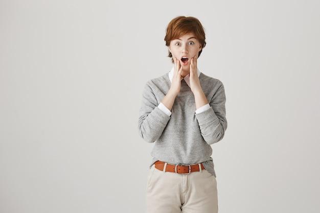 Fille rousse surprise et amusée avec une coupe de cheveux courte posant contre le mur blanc
