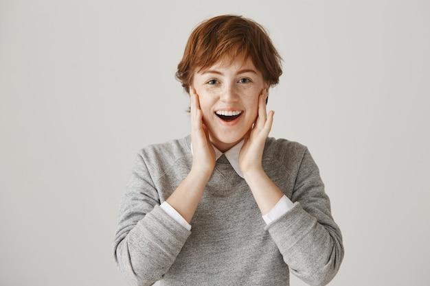 Fille rousse surprise et heureuse avec une coupe courte posant contre le mur blanc