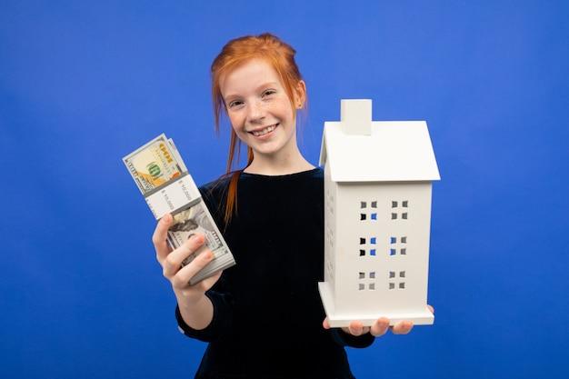 Une fille rousse surprise a reçu de l'argent sur un bleu. gain de logement de loterie