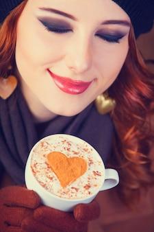Fille rousse avec une tasse de café rouge.