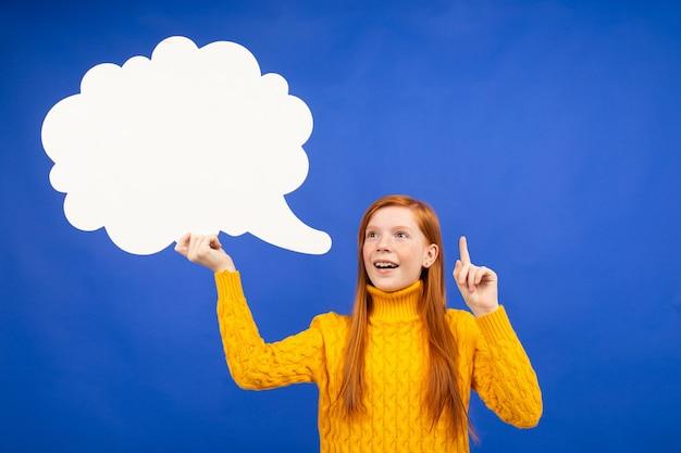Fille rousse tenant une bannière sous la forme d'un nuage montrant qu'elle a une idée sur bleu