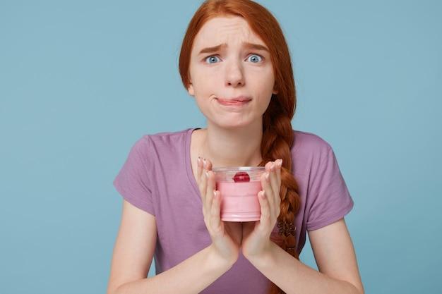 Fille rousse tient du yaourt aux fruits dans ses mains, semble inquiète, se mord la lèvre