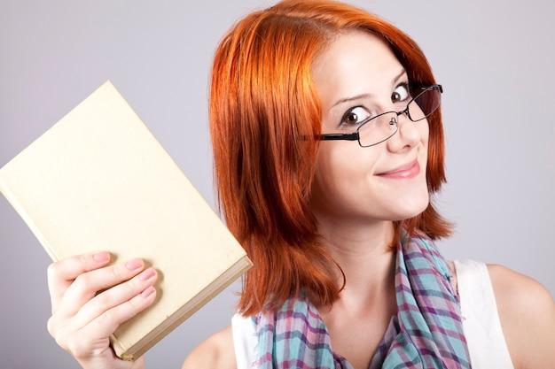 La fille rousse tient son livre à la main. studio shot.