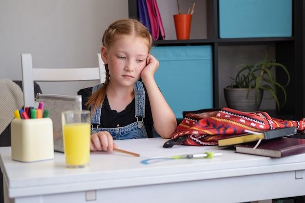 Fille rousse triste en sac à dos d'emballage de lunettes, se préparant à l'école. déprimé, épuisé.