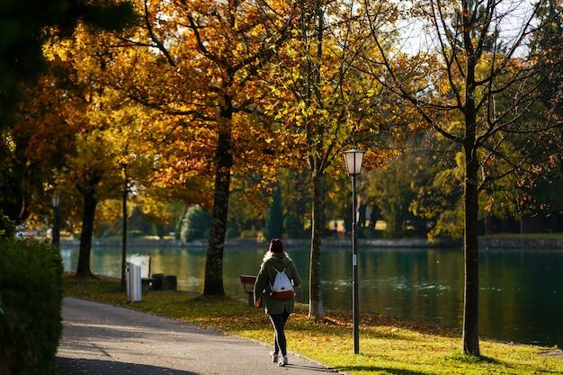 Fille rousse avec valise dans le parc en automne.