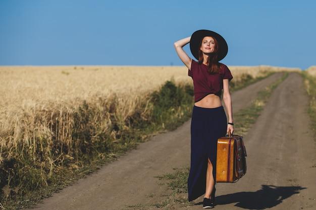Fille rousse avec valise à la route de campagne