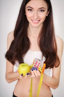 Fille avec ruban à mesurer et pomme pour concept de régime