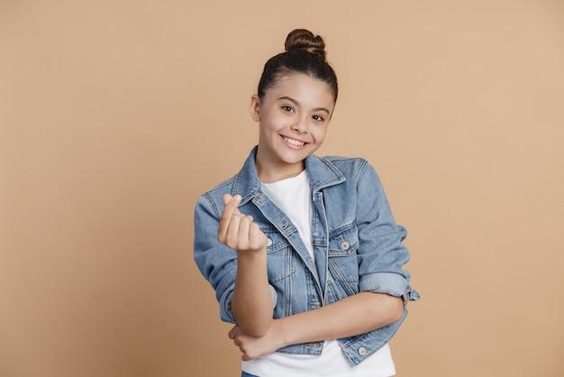 Une fille rusée et souriante montre un signe d'argent. fille gesticulant sur un fond marron