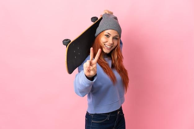 Fille russe adolescente isolée sur fond rose avec un skate faisant un geste de victoire