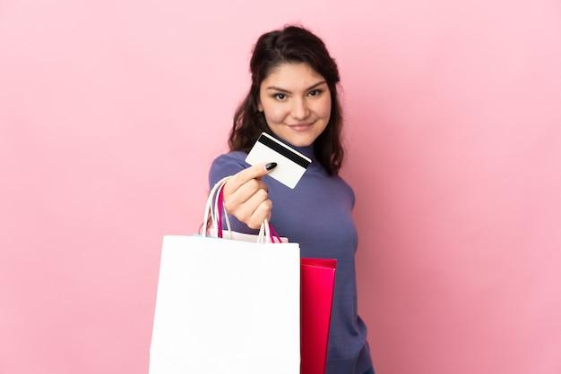 Fille russe adolescente isolée sur fond rose tenant des sacs à provisions et une carte de crédit