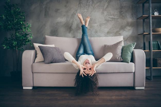 Fille s'amusant canapé allongé montrant ok-signe comme des verres dans l'intérieur de style industriel loft moderne