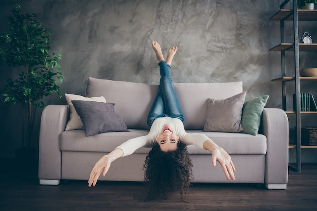 Fille s'amusant canapé couché dans le salon intérieur de style bois industriel loft moderne