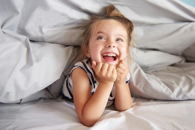 Fille s'amusant dans son lit