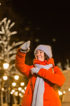 Fille s'amusant sur les lumières de décoration de noël rue jeune femme souriante heureuse portant élégant