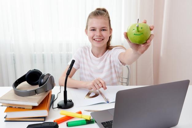 Fille s'amusant avec pomme verte tout en faisant ses devoirs, le concept de joie