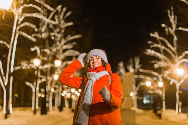 Fille s'amusant sur la rue des lumières de décoration de noël. jeune femme souriante heureuse portant une écharpe et une veste tricotées élégantes à l'extérieur. modèle en riant. scène de ville au pays des merveilles d'hiver, fête du nouvel an.