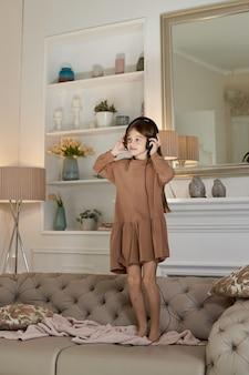 Fille s'amuse à la maison et saute sur le canapé en écoutant de la musique avec des écouteurs